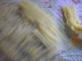 Теперь выложим второй слой желтой шерсти перпендикулярно первому. Не забываем выкладывать так, чтобы концы шерсти выходили за пределы шаблона на 1-1,5 см.